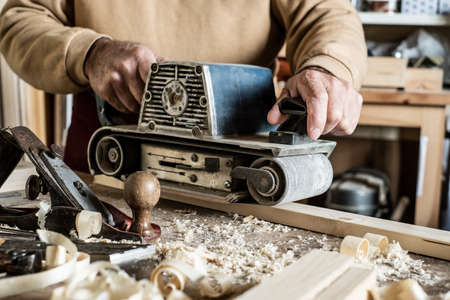 Electric belt sander, sanding machine in male hand. Processing of workpiece on light brown wooden table. Side view, close up Banque d'images - 138269179