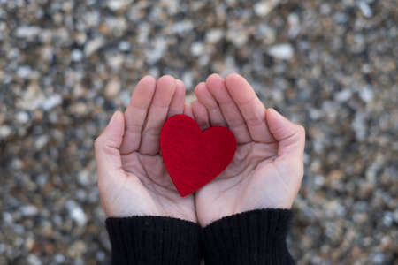red heart between the hands of a woman on a background of beach stones.concept of san valentine 免版税图像