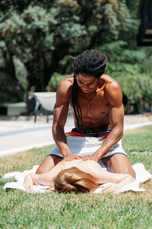 African-American man massaging a Caucasian womans back. 免版税图像