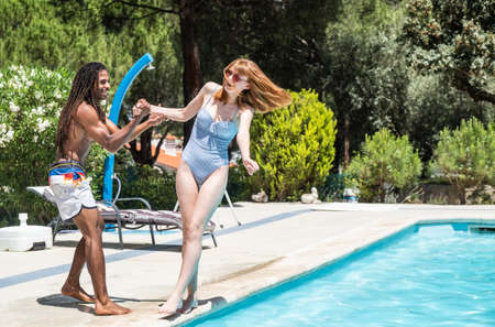 black guy with dreadlocks playing in a pool with caucasian girl. Stock Photo