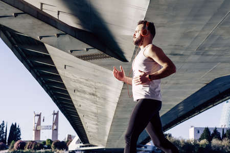 young man running in a white shirt across a bridge. He's listening to music and he's got some helmets on.