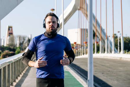 young man running and listening to music in an urban area Stock Photo