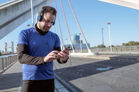 young man looking at his cell phone to listen to music while running through an urban area