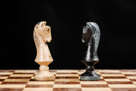 pieces of knights facing each other on a chessboard against a black background