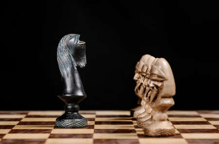 pawn chess pieces facing the knight on a chessboard Archivio Fotografico