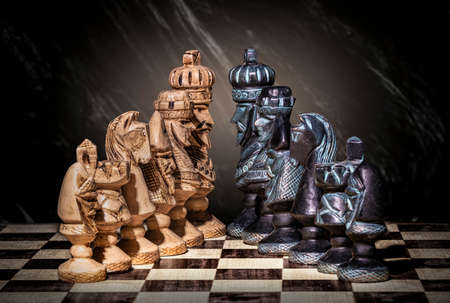brown chess pieces facing black pieces on an abstract background Archivio Fotografico - 151373581