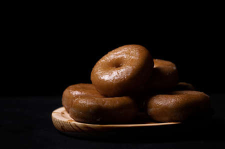 wooden board with donuts on a black background