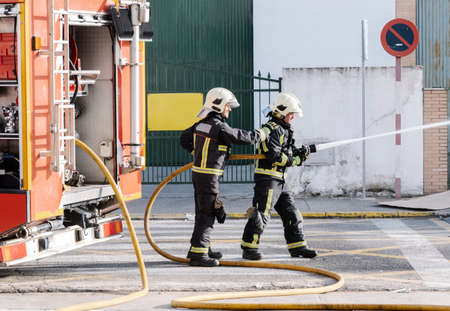 firefighters with a water hose pulling water to put out a fire Фото со стока