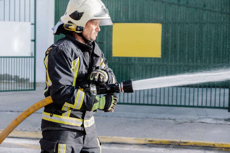 close-up of a fireman with a hose spreading water in a fire