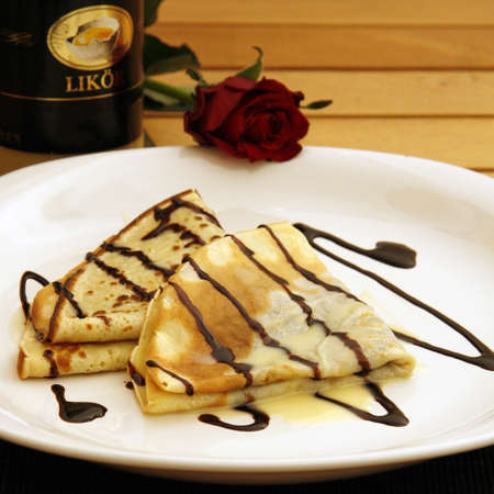 Pancakes with chocolate sauce and eggnog served on a plate