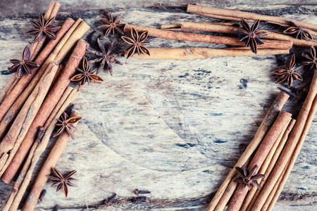 Artistic closeup of cinnamon and star anise seeds on a wooden background. Sunny still life photo. Stok Fotoğraf - 91662026