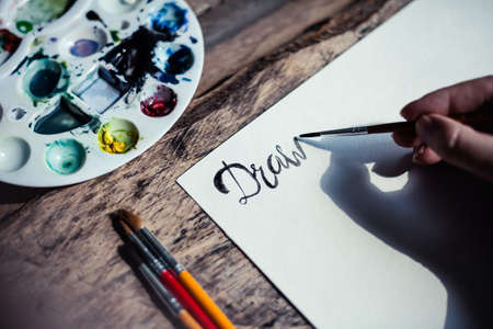 Closeup of  hand drawing letters. Artist durimg work process. Drawing process on wooden table with watercolor. Stock Photo