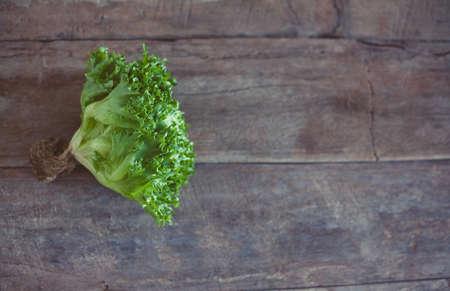 Letucce salad leaves on wooden background. Healthy food illustration. Salad ingridient topview.  Reklamní fotografie