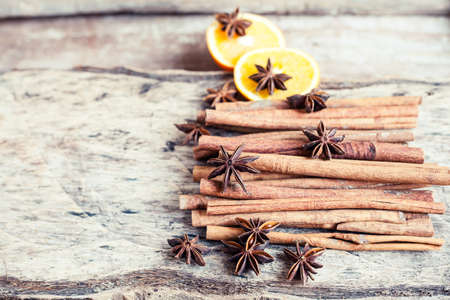 Artistic closeup of orange, cinnamon and star anise seeds on a wooden background. Sunny still life photo. Holiday spices.