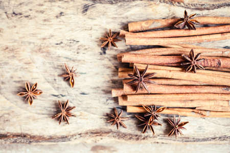 Artistic closeup of cinnamon and star anise seeds on a wooden background. Sunny still life photo. Stok Fotoğraf - 100544509