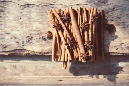 Artistic closeup of cinnamon and star anise seeds on a wooden background. Sunny still life photo. Stok Fotoğraf - 101503457