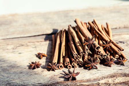 Artistic closeup of cinnamon and star anise seeds on a wooden background. Sunny still life photo. Stok Fotoğraf