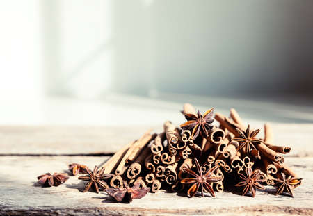 Closeup of cinnamon and star anise seeds on a wooden background. Sunny still life photo. Shallow depth of field