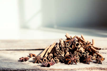 Closeup of cinnamon and star anise seeds on a wooden background. Sunny still life photo. Shallow depth of field Stok Fotoğraf - 101503463