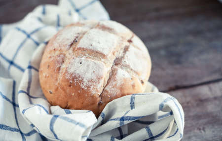 Close up photo of fresh baked bread on rustic wooden background with shallow depth of field. 写真素材