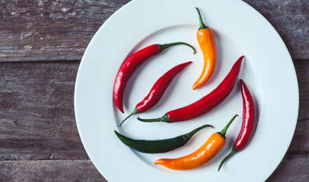 Hor chili peppers on a plate on a wooden background. Asian and mexican spice photo taken from the top. Stock Photo