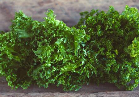 Letucce salad leaves on wooden background. Healthy food illustration. Salad ingridient closeup.