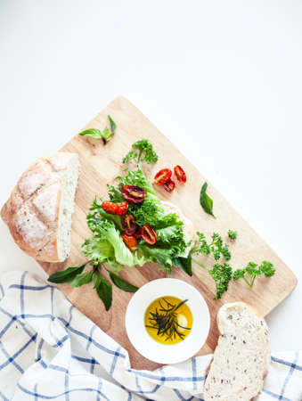 Italian cuisune ingredients - lettuce, baked tomatos, olive oil with rosemary, bread - on wooden board and copyspace for your text.