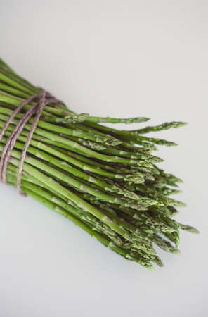 Bunch of fresh asparagus on white table. Healthy food photo series. Standard-Bild - 101513534