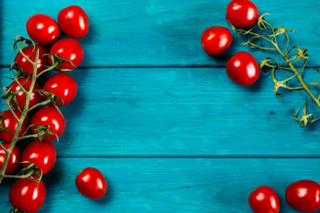 Farm grown cherry tomatos on wooden background. Natural food photography with shallow depth of field. Stock Photo
