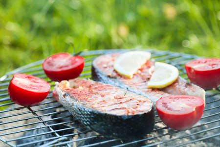 Salmon preparation process on wooden grill. Grilled fish steaks on fire. Shallow depth of field Stock Photo
