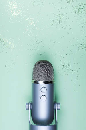 Closeup of professional microphone on mint background. Podcast studio concept. Electronic mic top view.