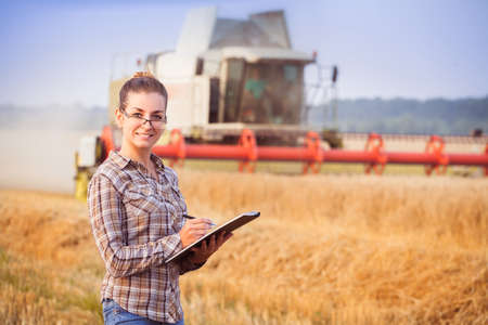 tied in: Pretty farmer girl in glasses with hair tied in a ponytail keeps a harvest accounting in the folder. Sunny day. Horizontal. Image released. Image released.