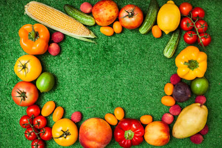 space for text: group of fruits and vegetables arranged in a circle on a background of green grass. Free space for text in the middle.Group of fruits and vegetables