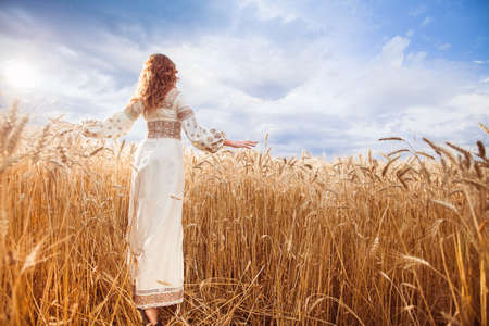 Pretty woman wearin? a embroidered dress with braid walking with her back to the camera among of golden field and pushes wheat Stock Photo