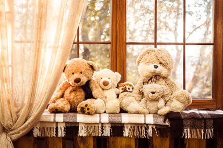 plush toys: Teddy bears and other plush toys sitting at the windowsill. Stock Photo