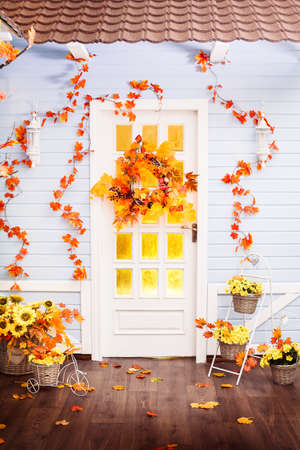 House with tiling roof, blue wooden walls, entwined with autumn leaves. Wicker wreath decorated with vegetables hanging on the door.
