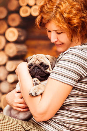 carlin: White puppy pug hiding on arms of loving owner