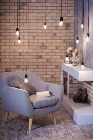 illuminate: Cozy place for reading on gray chair in front of modern fireplace. Loft style.