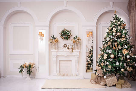 Majestic white hall with classical fireplace, arches and mirrors. At the wall hanging Christmas wreath. New Year tree stands in the corner of room. Stock Photo