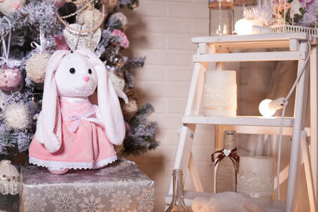 rabbit standing: Christmas pink dressed rabbit standing on a gift box under holiday tree, decorated in rustic and shabby chic style