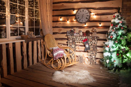 rocking chair: Wooden rome in rustic house with wooden fireplace, decorated Christmas tree and rocking chair