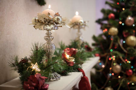 holders: Winter candle holders with burning candles at the Christmas tree background