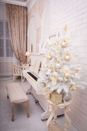 christmas tree decoration: White piano near decorated Christmas tree in large hall with brick wall. Xmas background. Winter time