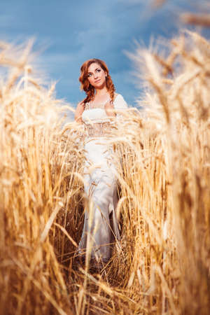 Pretty woman in embroidered gown standing among of wheat field and looking down. Model released
