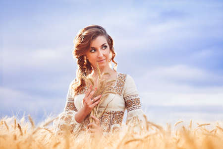 Pretty woman dressed in embroidered gown with tress standing among of wheat field and huging a sheaf of wheat