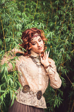 Hippie girl standing under the willow tree ruffling long red curling hairs. Decorations in favorable hippies' style, bracelet, trinket, bauble, chaplet, beads. Vertical. Image released