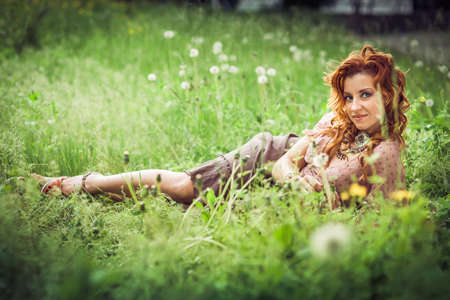 blowball: Hippie girl with red curling hairs lying on the green grass with blowball and smiling. Horizontal. Image released