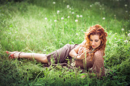 blowball: Hippie girl with red curling hairs lying on the green grass with blowball and smiling Stock Photo