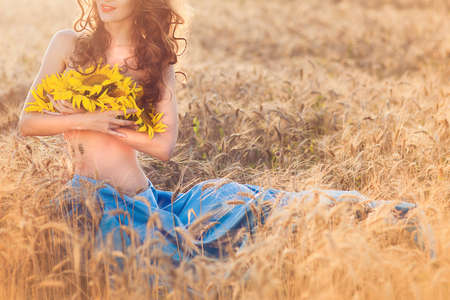 Unrecognized young girl pressed to itself sunflowers sitting at the wheat field. Nature concept. Horizontal Stock Photo