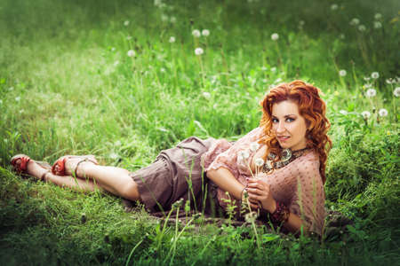 Hippie girl with red curling hairs lying on the green grass with blowball and smiling. Horizontal. Image released